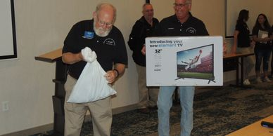 Two NCARCA members raffling off a TV.