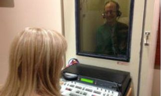 Lisa Jones BC-HIS, performing a Hearing Test Inside Hearing Test Booth in Orange City, Florida