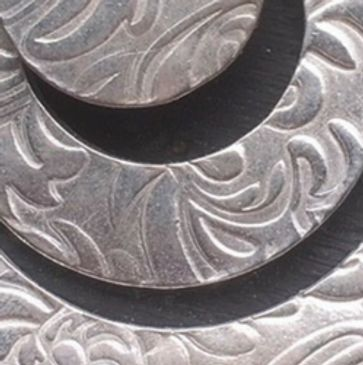 created from a circle of textured silver clay, then stringed together so they overlap.