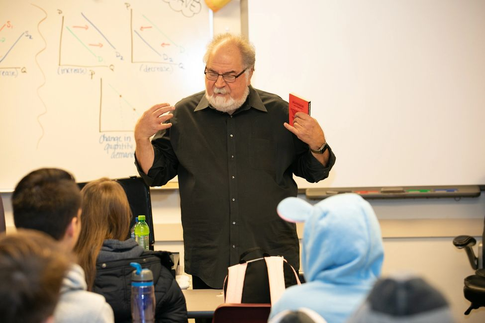 Lew engages a class of high-school students (including one with ears on her hood!).