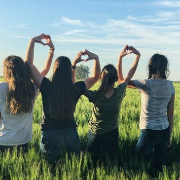 women forming heart gestures during daytime Photo by Melissa Askew on Unsplash