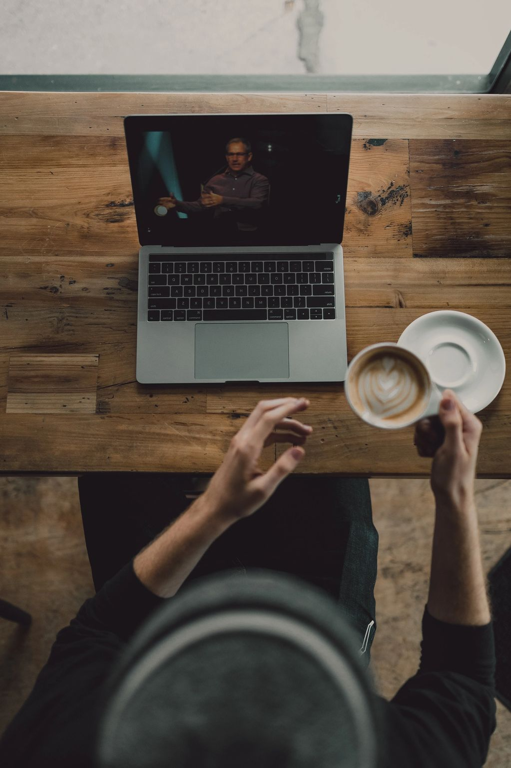 Person holding cup of latte while facing MacBook nathan-ansell-JvbNsRCXXic-unsplash