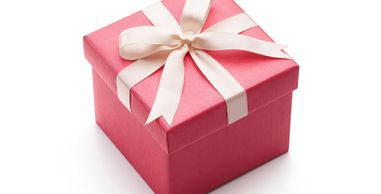 Pink present wrapped with white ribbon to denote brand packaging and strategy.