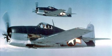 Two U.S. Navy Grumman F6F-3 Hellcats in tricolor camouflage.