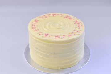 red velvet cake with a cream cheese buttercream covered in pink and white sprinkles