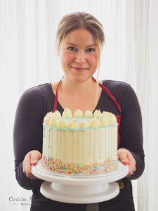 pastry chef in vienna holding custom drip cake with sprinkles and organic dairy