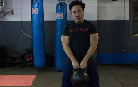Man lifts kettlebell to waist level.