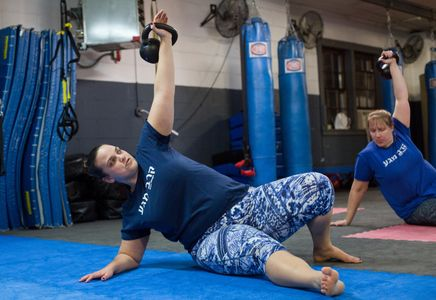 Woman lifts kettlebell above her head while leaning on the ground.