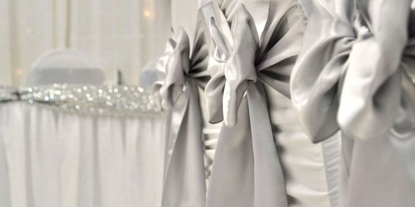 white chair covers and silver satin sashes tied in bows, onsite services with setup and tear down