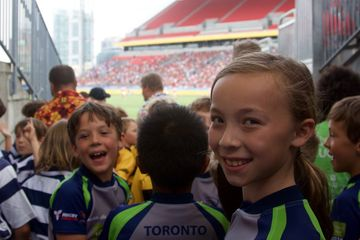 Youth at Toronto City walk professional rugby players onto the field at BMO