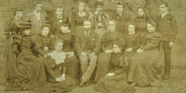 Photograph of the teaching staff of All Saints School, Bradford, taken in the playground around 1900