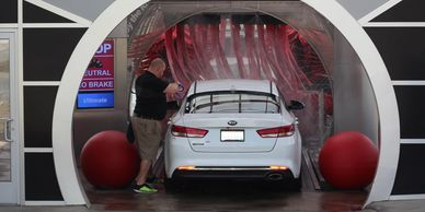 Waves Express Car Wash teammate removing antenna from customer vehicle as it enters the tunnel wash.