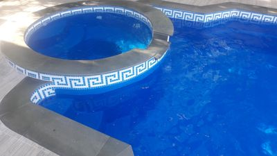 Prestige Composite Swimming Pool Cesar with Jacuzzi/waterfall. Mosaic waterline. Top grey sandstone
