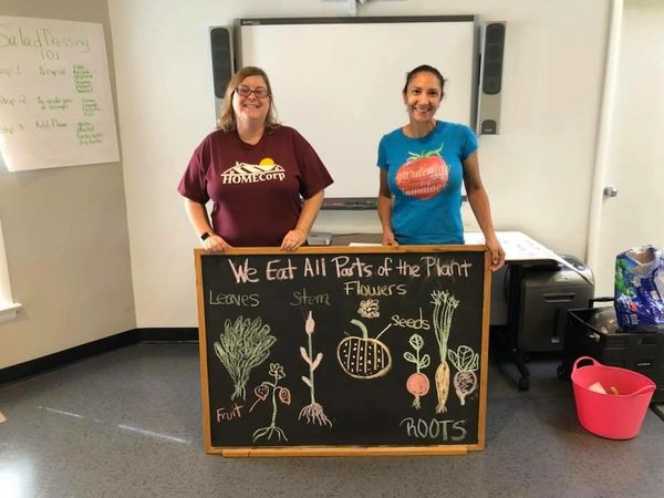 HOMECorp employee and volunteer standing in front of a chalkboard. Picture taken at a workshop for g