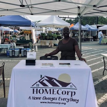 HOMECorp employee standing at a table with the HOMECorp logo on the tablecloth.