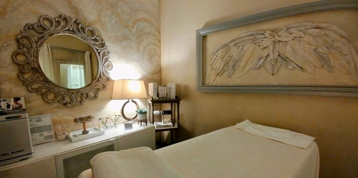 A large piece of Angel wing art in a soft muted grey frame graces the main wall as the focal point of the treatment room. The spa bed is draped in soft cream and white linens creating a comfortable and inviting feeling of relaxation.