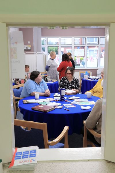 People sitting at table for day centre open day