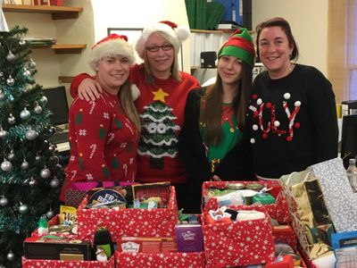 Office staff in Christmas hats delivering presents