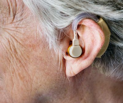 Close up of hearing aid in older person's ear