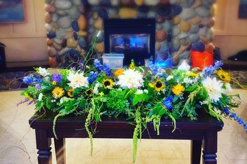 Cascading arrangement of blue, white and green flowers from our custom florists.