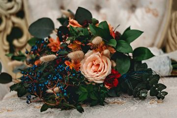 Beautiful bridal bouquet featuring peach roses, delicate blue accents and greenery from our floral s