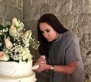 Owner Kimberly hand pipping finishing touches on wedding cake.