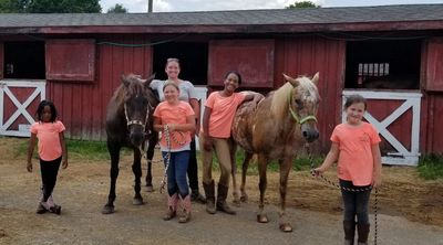 campers posing with instructor and 2 horses