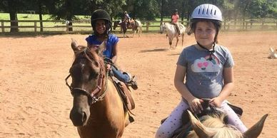 several campers riding horses in outdoor arena