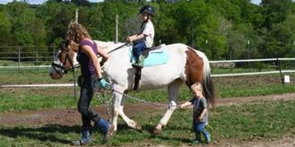 instructor leading child on paint horse while another child walks along side