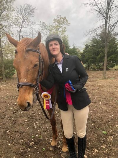 Smiling woman holding winning ribbons stands by chestnut mare