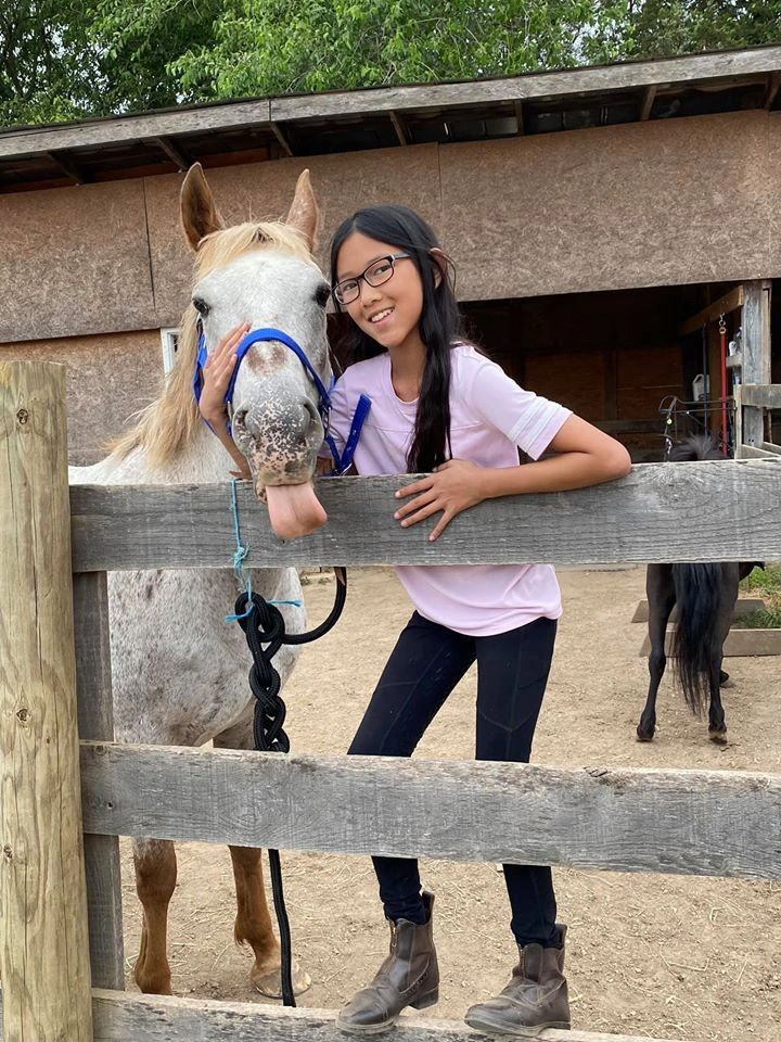 Young student poses with appalosa mare sticking her tongue out