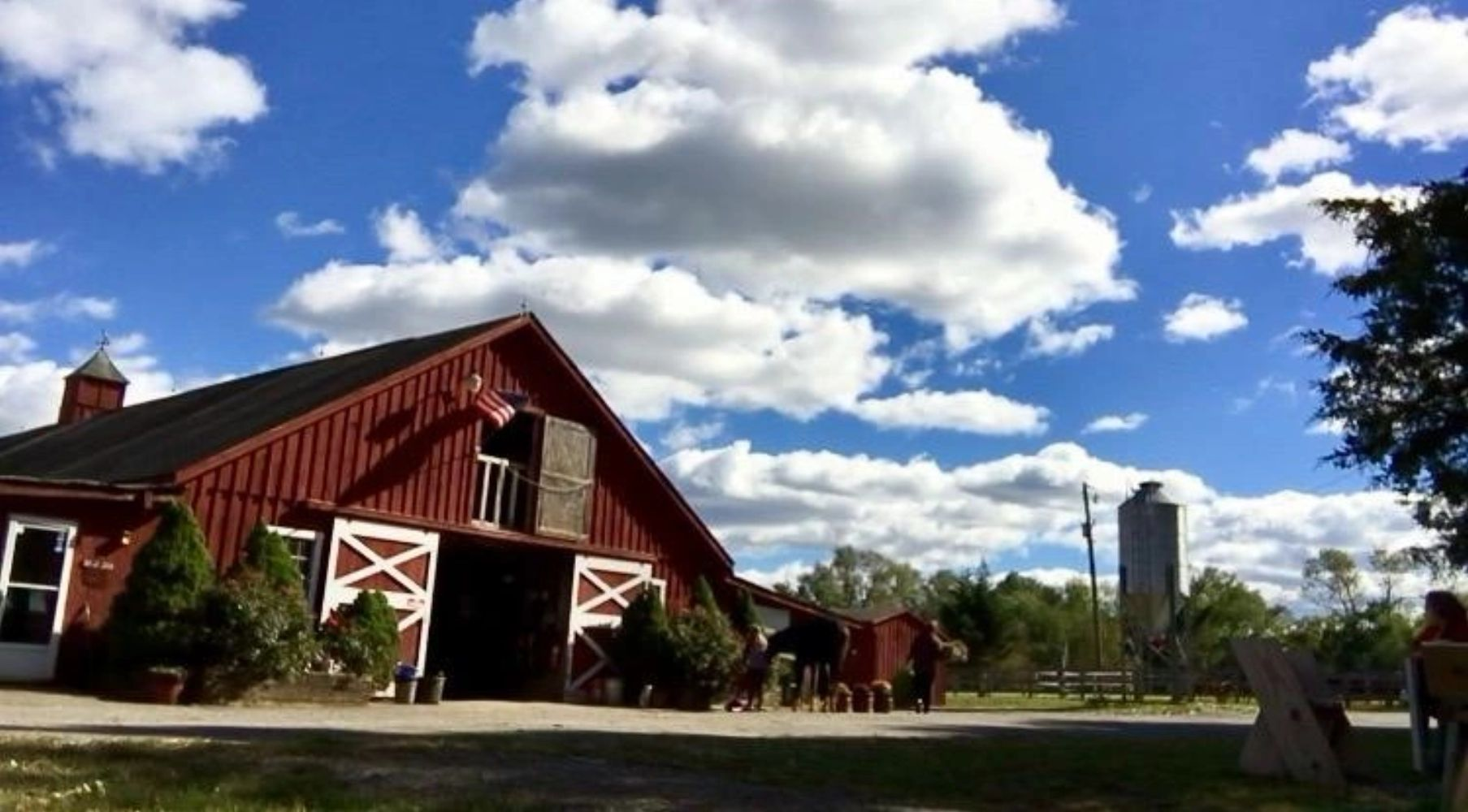 horse and owners in daily life in front of red barn with blue sky