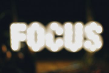 Out of focus sign saying 'Focus' stefan-cosma-362616-unsplash Sabrestorm Stories Author Coaching