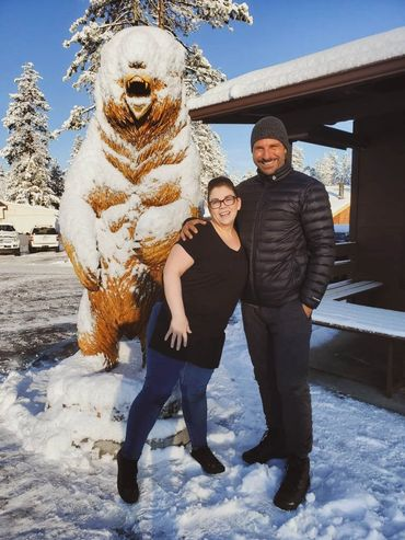Grizzly Manor Cafe manager Janelle Nordine and actor Ed Quinn in front of Wendell the Bear