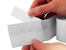 A woman shows how to remove the backing from white tape