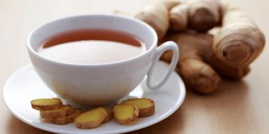 Herbal tea in a white cup and saucer with fresh ginger root in the background