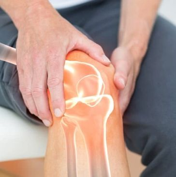 A patient sits on a treatment table and holds their knee with a stylised overlay of their joints showing through