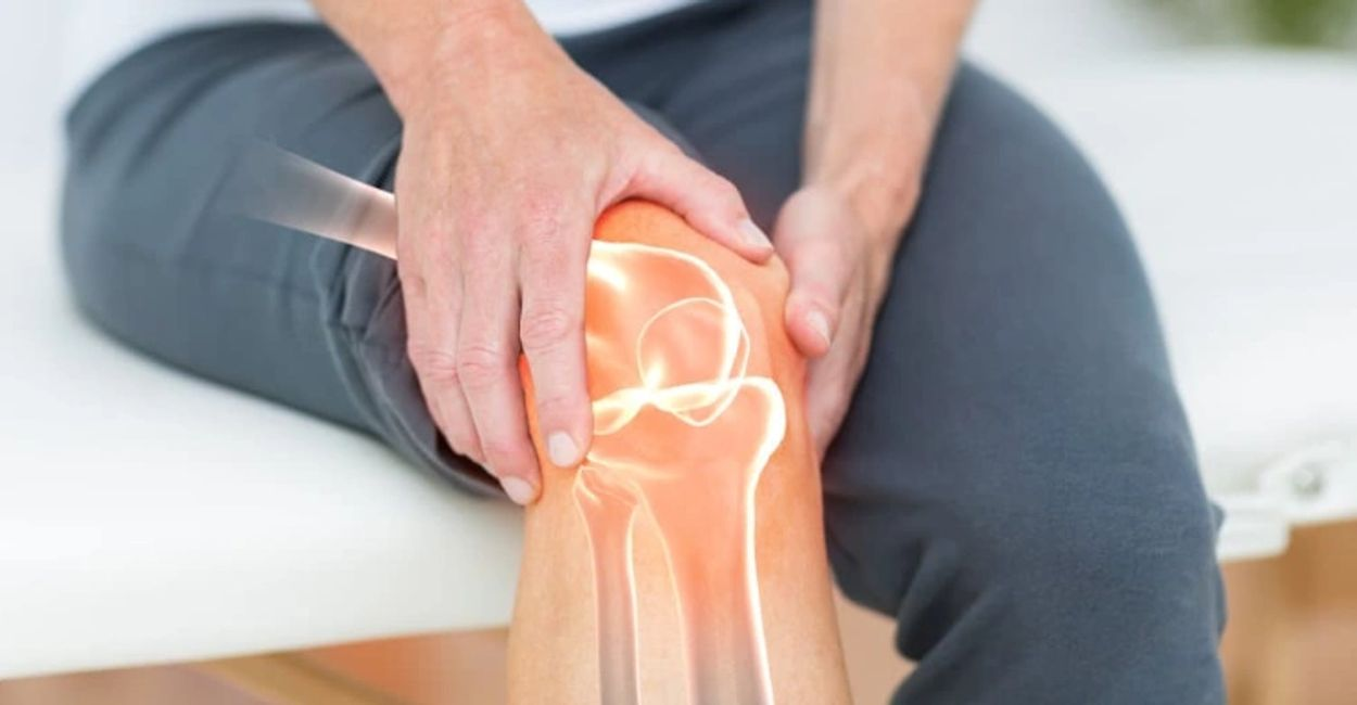 A patient sits on a physio treatment table and holds their knee while a stylised image of their joints shows through