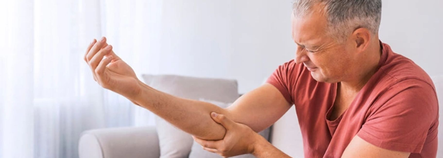 A man with grey hair and a red t-shirt holds his elbow in pain