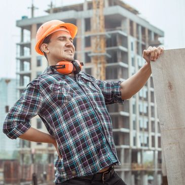 A construction worker with an orange hardhat and plaid shirt holds his lower back in pain