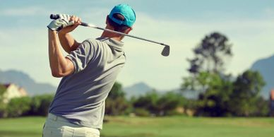 A golfer wears a blue hat and looks as he takes a swing