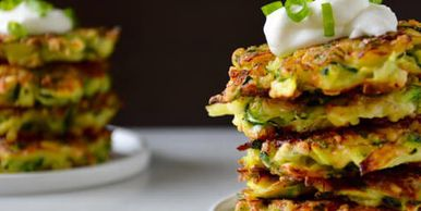 Zucchini fritters stacked up with a sour cream and shallot garnish on top