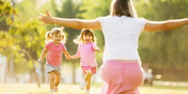 A mother crouches and holds her hands out as two little girls run towards her