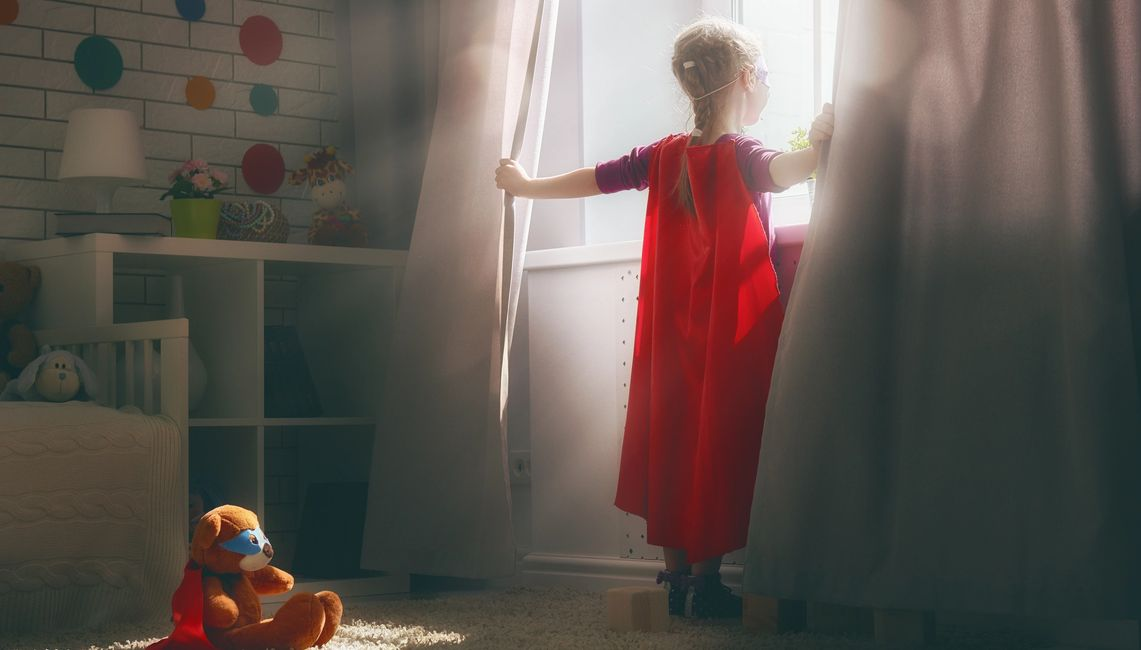 picture of a child wearing a superhero costume looking out a window.