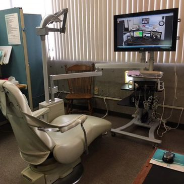 State of the art dental exam office with massage chair, x-ray, and monitor.