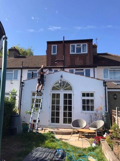 Cleaning windows up a telescopic ladder