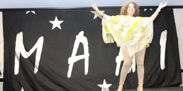 Image of Renée Lacy on stage wearing a yellow and cream striped cape and tan leggings.
