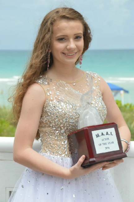 MAAI Actor of the Year model holding trophy, beach/ocean in background