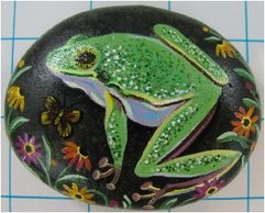 Hand painted stone with acrylics. Tree frog with daisies.