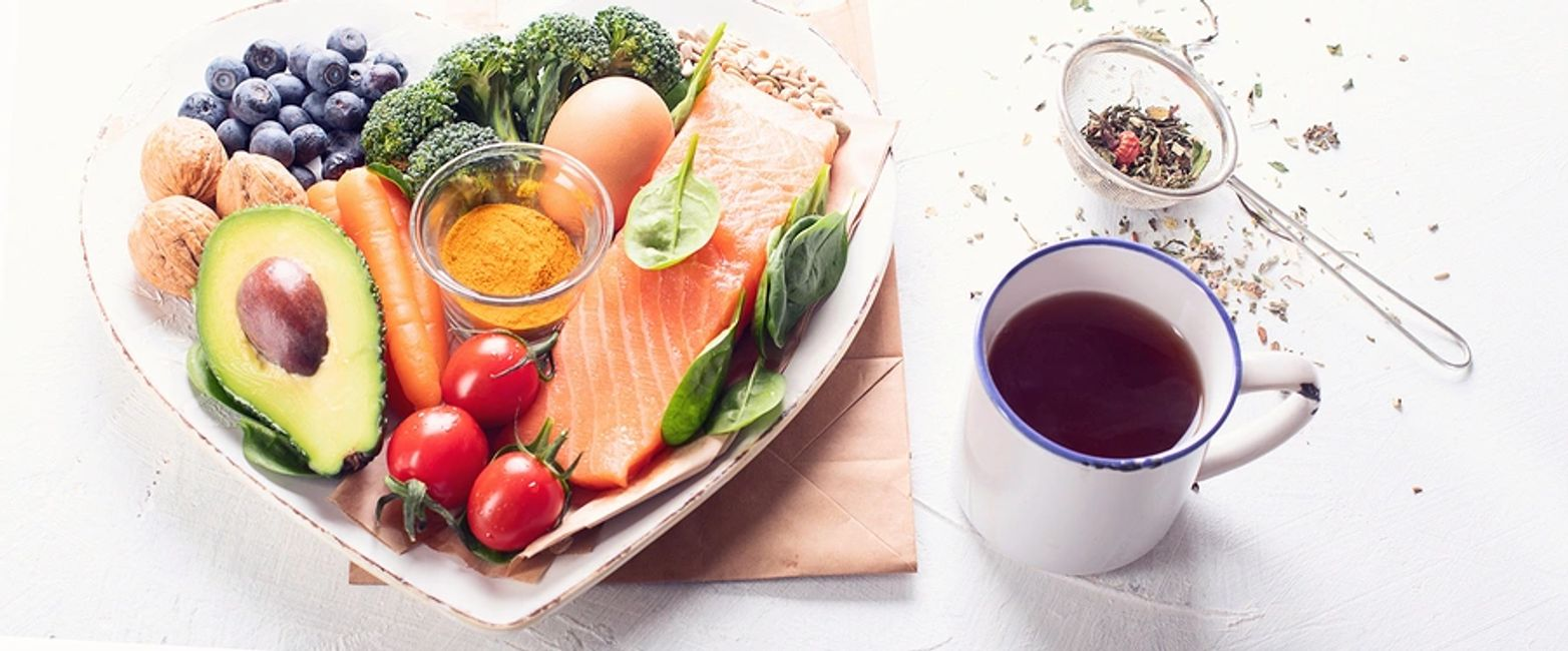 A heart shaped plate of nutritious, healthy food with a cup of herb tea.